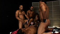 Stunning black whore with fake titties gives head to lusty boys